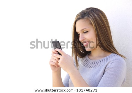 Happy woman texting on a smartphone looking at phone on a white wall