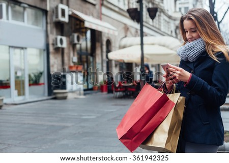 Happy woman texting on her mobile phone on the street with copy space - stock photo