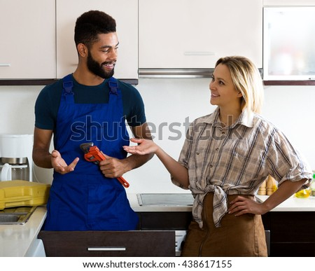 Happy woman thanking black professional plumber for work