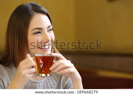 Happy woman thinking and holding a cup of tea in a coffee shop with a warmth background