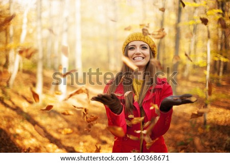 Happy woman throwing leaves - stock photo