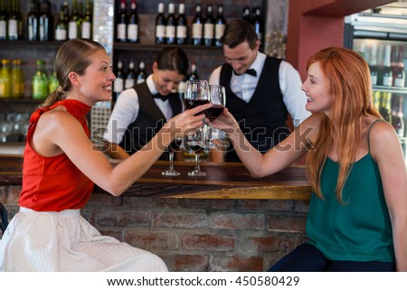 Happy woman toasting a red wine glass at bar counter in bar