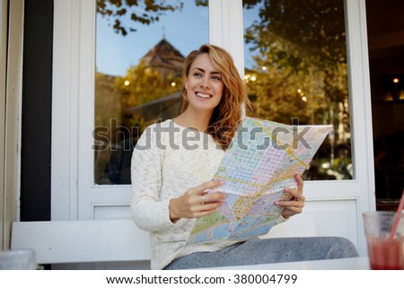 Happy woman tourist searching on the map road to hotel in a foreign city while lunch in modern restaurant, joyful female traveler waiting for the beginning of excursion while sitting in sidewalk cafe - stock photo