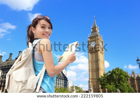 Happy woman travel in London with Big Ben tower, she look map and smile to you, asian - stock photo