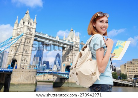 Happy woman travel in London with tower bridge, and smile to you, caucasian beauty - stock photo