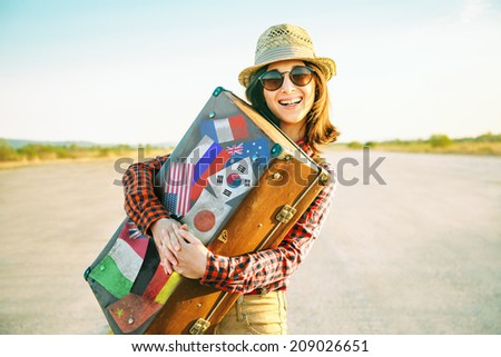 Happy woman traveler embraces a vintage suitcase on road. Suitcase with stamps flags representing each country traveled. - stock photo