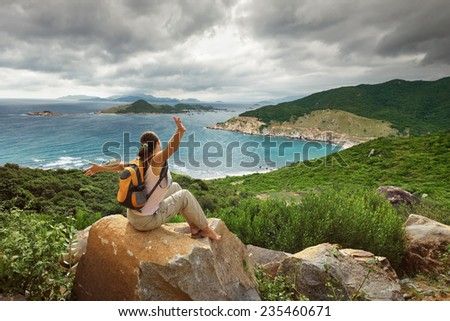 Happy Woman traveler looking on the edge of the bay and mountains in the background - stock photo