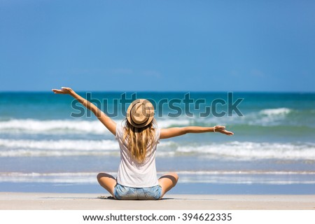 Happy woman traveler relaxing on a perfect beach - stock photo