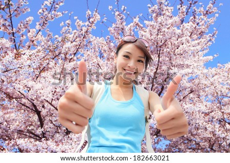 Happy woman traveler show thumb up with  cherry blossoms tree on vacation - stock photo