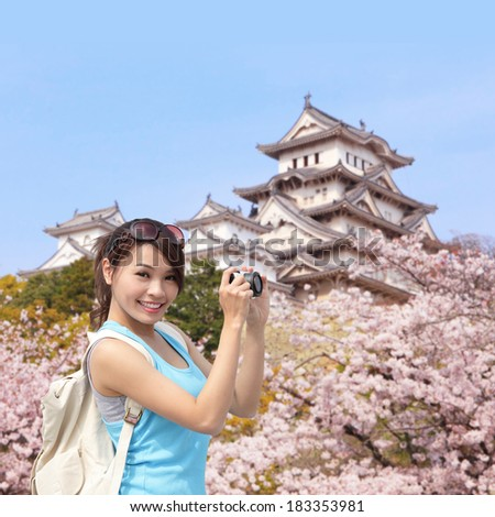 Happy woman traveler take photos by camera with cherry blossoms tree and castle on vacation while spring - stock photo