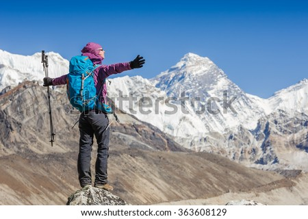 Happy Woman Traveler with Backpack hiking in Mountains with Everest background. mountaineering sport lifestyle concept - stock photo