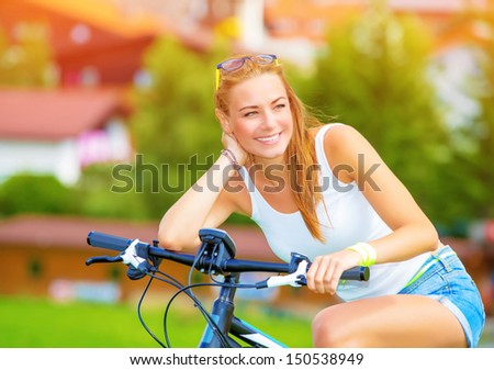 Happy woman traveling on bicycle along Europe, active lifestyle, enjoying riding on pushbike, summer adventure, travel and tourism concept - stock photo