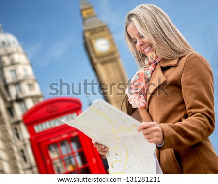 Happy woman traveling to London and holding a map - stock photo