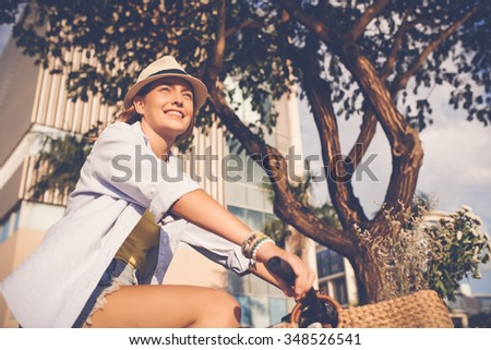 Happy woman travelling by bike through the city - stock photo