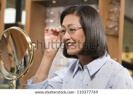 Happy woman trying on glasses