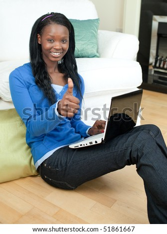 Happy woman using a laptop sitting on the floor in the living-room - stock photo
