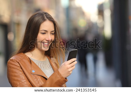 Happy woman using a smart phone in the street with an unfocused background - stock photo