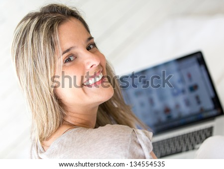 Happy woman using her laptop computer at home - stock photo