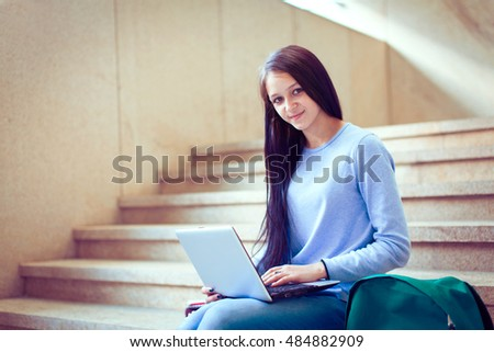Happy woman using laptop computer outdoors