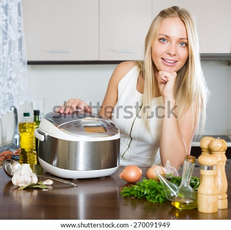 Happy woman using new  slo-cooker in kitchen - stock photo