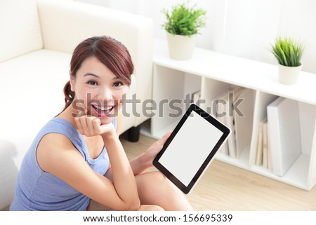 happy woman using tablet pc on sofa in the living room, empty computer screen is great for your design copy space, asian beauty