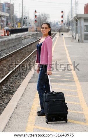 Happy woman waiting for a train - stock photo