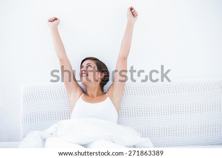 Happy woman waking up at home in the bedroom - stock photo