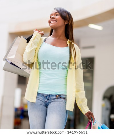 Happy woman walking at the shopping center holding bags - stock photo