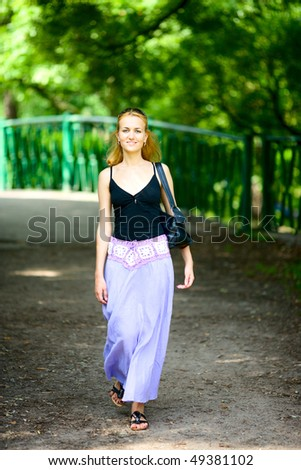 Happy woman walking in summer park smiling