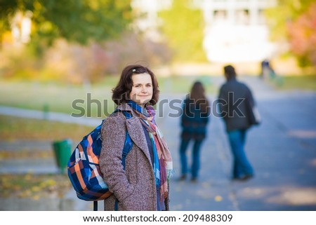 Happy woman walking outdoors with her family in background on an autumn day. - stock photo