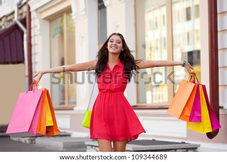 happy woman walking with shopping bags - stock photo