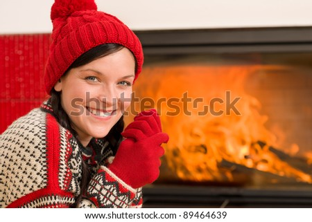 Happy woman warming up by home fireplace wear Christmas sweater - stock photo