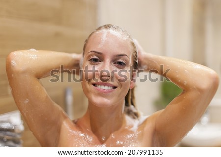 Happy woman washing hair under shower - stock photo