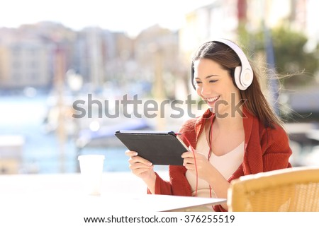 Happy woman watching media content in a tablet sitting in a bar terrace in a sunny day in a port  - stock photo