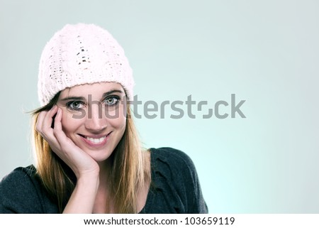 happy woman wearing a winter cap on light blue background - stock photo