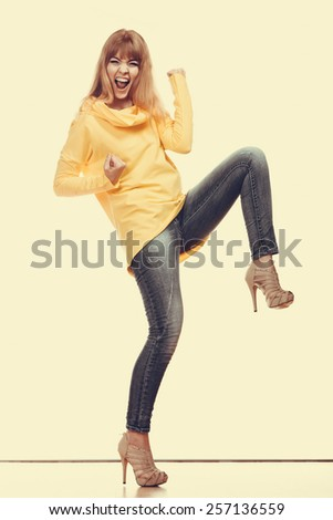 Happy woman wearing denim pants high heels. Girl in full length celebrating success clenching fist - stock photo