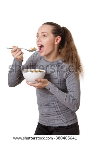 happy woman wearing fitness clothes eating cereal