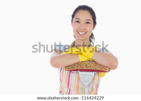 Happy woman wearing gloves and apron leaning on mop - stock photo