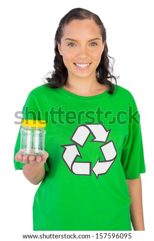 Happy woman wearing green recycling tshirt holding jar against white background - stock photo