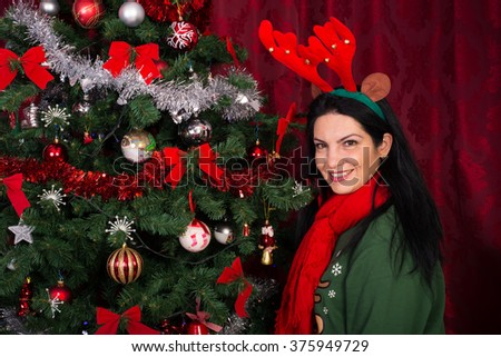 Happy woman wearing reindeer ears standing near Christmas tree in home