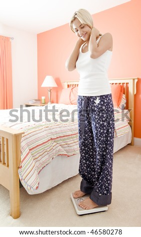 Happy woman weighing herself in her bedroom and looking down at the scale. Vertical format. - stock photo