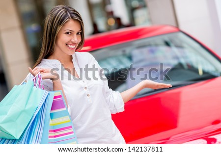 Happy woman winning a car for shopping at the mall - stock photo