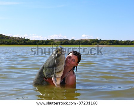 Happy woman with a catfish she has just caught - stock photo