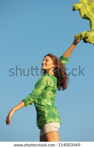 Happy woman with a colored tissue against blue sky - stock photo
