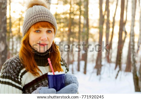 Happy  woman with a cup of hot tea on snowy winter walk in nature. Concept of frost winter season.