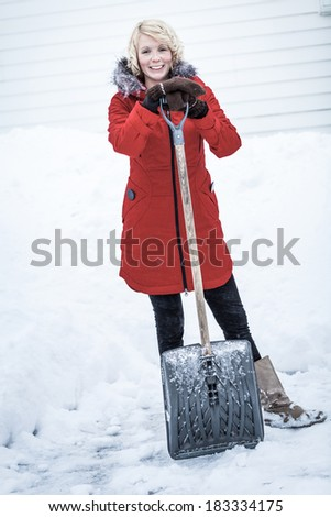 Happy Woman with a Shovel in a Parking lot. She's done with shoveling for today ! - stock photo
