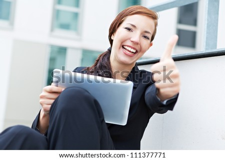 Happy woman with a tablet pc holding her thumbs up - stock photo
