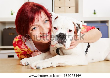 Happy woman with a young albino boxer dog in her office - stock photo