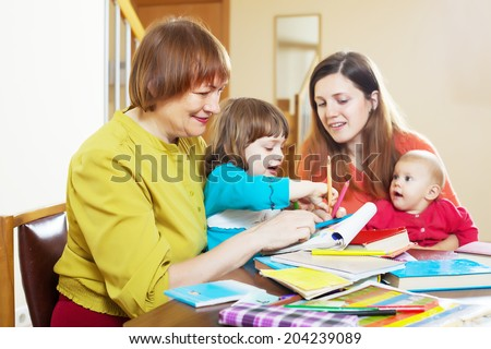 Happy woman with adult daughter and two children playing at home interior. Focus on mature - stock photo
