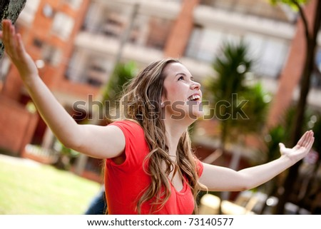Happy woman with arms up and smiling outdoors